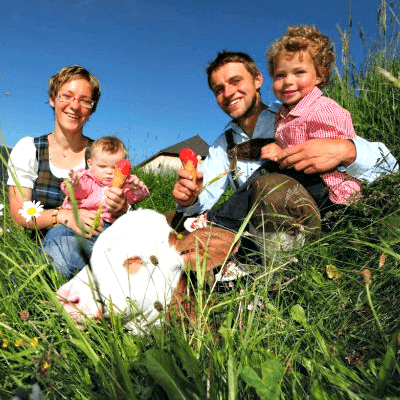 Happy farmer's family poses with an ice cream in the pasture